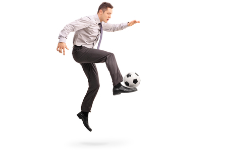 midair: Full length profile shot of a young businessman playing football shot in mid-air isolated on white background Stock Photo