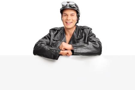 motociclista: Young motorcyclist in a black leather jacket posing behind a blank signboard isolated on white background