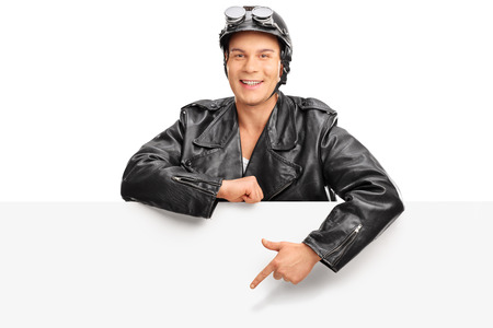 leather: Young biker in a black leather jacket standing behind a blank billboard and pointing towards it with his finger isolated on white background