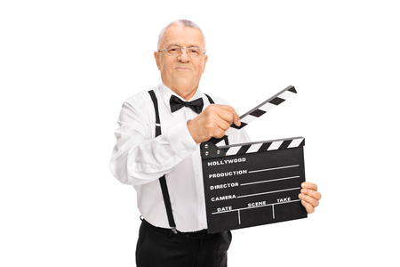filming: Elegant mature man holding a movie clapperboard and looking at the camera isolated on white background