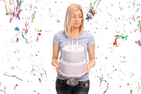 tortas de cumpleaños: Triste joven sosteniendo un pastel de cumpleaños y mirando hacia abajo con un montón de serpentinas confeti volando alrededor de ella aislados sobre fondo blanco