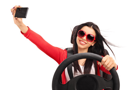distracted: Young cheerful woman taking a selfie while driving a car isolated on white background