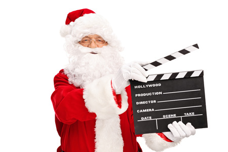 christmas movies: Studio shot of Santa Claus holding a movie clapperboard and looking at the camera isolated on white background
