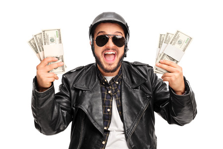 lot of: Happy young male biker holding few stacks of money and looking at the camera isolated on white background Stock Photo