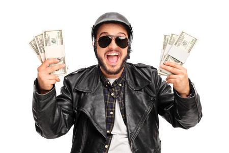 mucho dinero: motorista varón joven feliz celebración de unos montones de dinero y mirando a la cámara aislada en el fondo blanco