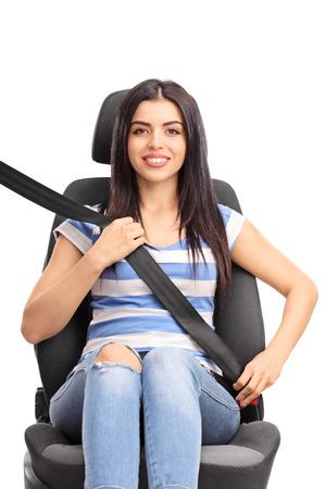 cinturon seguridad: Estudio tiro vertical de una mujer joven sentada en un asiento de seguridad abrochado con el cinturón de seguridad aisladas sobre fondo blanco