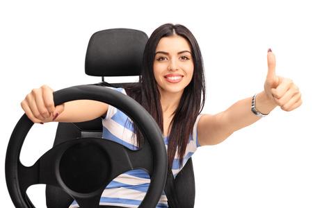 若い陽気な女性車両を運転、白い背景で隔離を親指をあきらめる