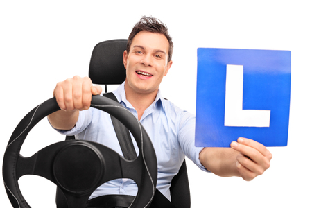 Young man pretending to drive seated on a car seat and holding an L-sign isolated on white background Zdjęcie Seryjne