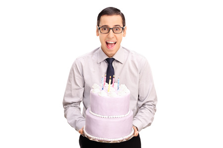 birthday cakes: Cheerful young man holding a birthday cake and looking at the camera isolated on white background Stock Photo