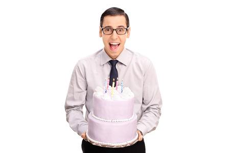 tortas de cumpleaños: Hombre joven alegre que sostiene una torta de cumpleaños y mirando a la cámara aislada en el fondo blanco