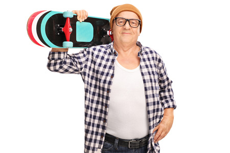 shoulder carrying: Senior hipster carrying a skateboard over his shoulder and looking at the camera isolated on white background