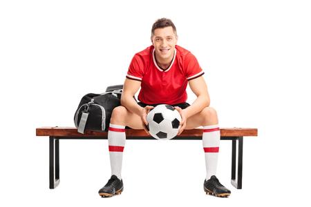 futbolista: Futbolista joven que sostiene una bola y sentado en un banco de madera aislada sobre fondo blanco Foto de archivo