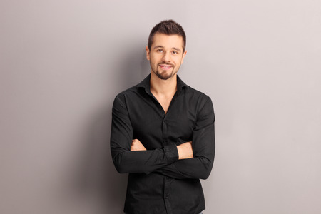 shirt: Handsome young man in a black shirt leaning against a gray wall and looking at the camera