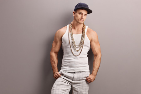 Young muscular rapper with a gold chain leaning against a gray wall and looking at the camera Stock Photo