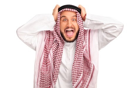 in shock: Studio shot of an outraged young Arab posing with his hands on his head isolated on white background