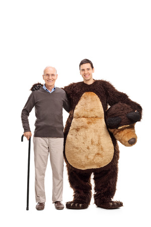head of animal: Full length portrait of a senior gentleman with a cane posing with a man in a bear costume isolated on white background