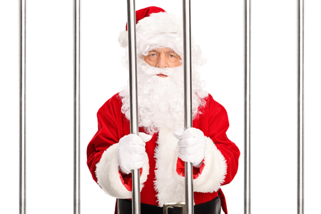 white bars: Studio shot of Santa Claus standing in a jail cell behind bars isolated on white background