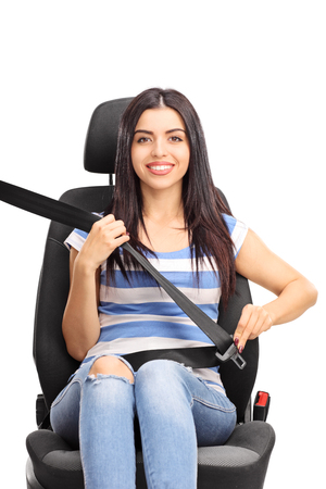 cinturon de seguridad: Tiro vertical de una mujer joven sentada en un asiento de seguridad abrochado con el cinturón de seguridad y mirando a la cámara aislada en el fondo blanco