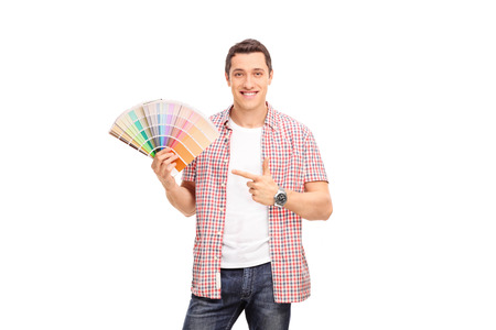 color swatch: Cheerful young man holding a color swatch in one hand and pointing towards it with the other isolated on white background