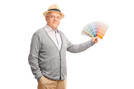 color swatch: Studio shot of a senior gentleman holding a color swatch and looking at the camera isolated on white background Stock Photo