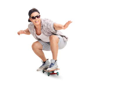 joy: Studio shot of a young joyful skater riding a skateboard isolated on white background