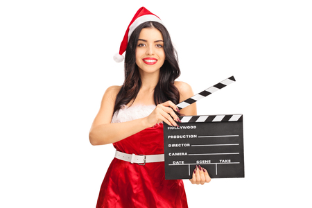 action movie: Young woman in Santa costume holding a movie clapperboard and looking at the camera isolated on white background