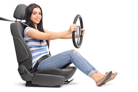 Młoda wesoła kobieta udając napęd siedzi na siedzeniu samochodu na białym tle