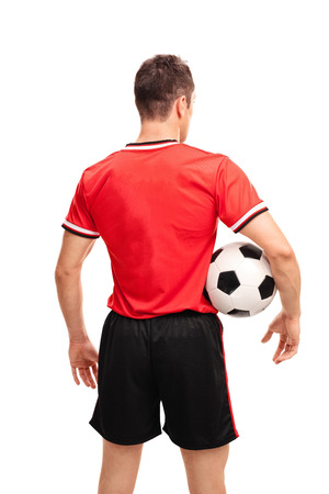Rear view vertical shot of a young football player holding a ball isolated on white background Stock Photo