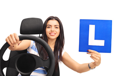 Young woman holding a steering wheel and an L-sign seated on a car seat isolated on white background