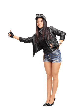 biker girl: Full length portrait of a female biker in black leather jacket hitchhiking with her thumb isolated on white background