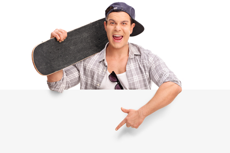 billboard background: Cocky young skater standing behind a blank signboard and pointing on it with his hand isolated on white background