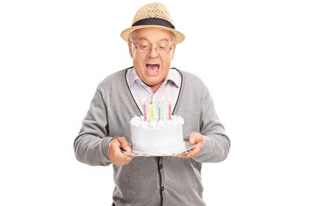 白い背景で隔離のケーキ誕生日にろうそくを吹いて楽しい上級紳士