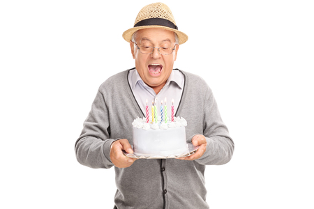 1 mature man: Joyful senior gentleman blowing candles on his birthday cake isolated on white background Stock Photo
