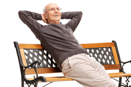 carefree: Relaxed senior gentleman sitting on a wooden bench and looking in the distance isolated on white background Stock Photo