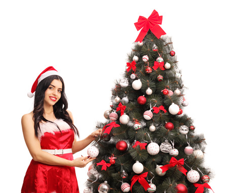 decorating christmas tree: Young woman in Santa costume decorating a Christmas tree Stock Photo
