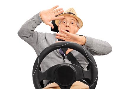cinturón de seguridad: Altos hombre asustado sentado en un asiento de seguridad abrochado con el cinturón de seguridad y gesticulando con las manos aisladas sobre fondo blanco