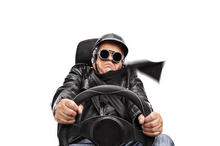 白い背景に分離された車の座席に座っている非常に高速黒革のジャケットとゴーグルの運転で年配の男性 写真素材