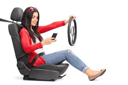 cinturon de seguridad: Mensajes de texto Mujer joven y un conductor sentado en un asiento de seguridad abrochado con el cinturón de seguridad aisladas sobre fondo blanco Foto de archivo
