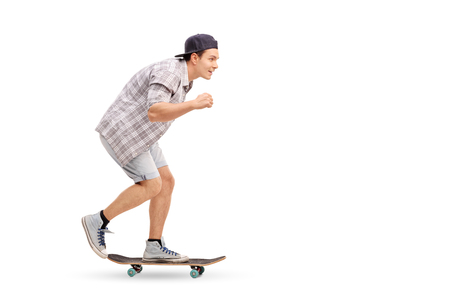 profile: Full length profile shot of a young man riding a skateboard and smiling isolated on white background