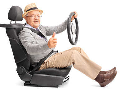 posing  agree: Senior gentleman pretending to drive seated on a car seat and giving a thumb up isolated on white background Stock Photo