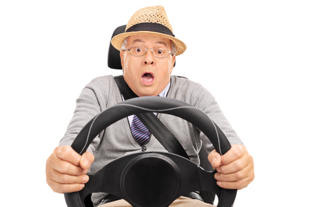 scared: Scared senior holding a steering wheel and pressing the brake pedal to avoid a car crash isolated on white background