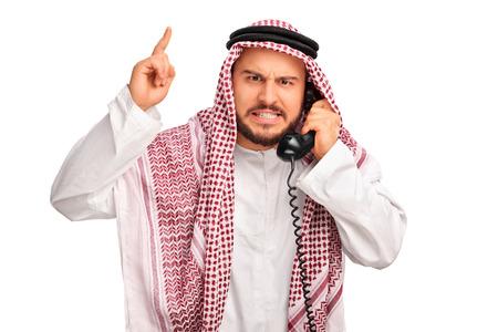 enojo: Studio foto de una conversación árabe enojado en el teléfono y amenazando con el dedo aislado en el fondo blanco
