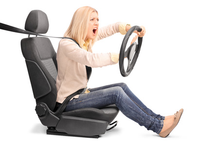 honking: An outraged young woman pretending to drive and honking the horn isolated on white background Stock Photo