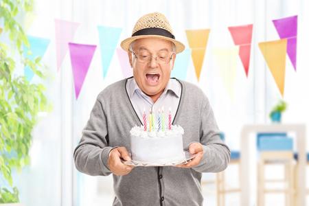 彼の誕生日にケーキのホームでろうそくを吹いて喜んで上級紳士 写真素材