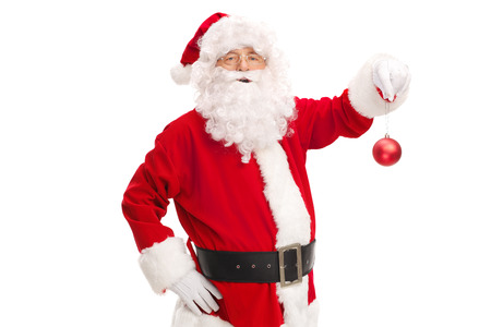 holding a christmas ornament: Studio shot of Santa Claus holding a red Christmas ball and looking at the camera isolated on white background Stock Photo