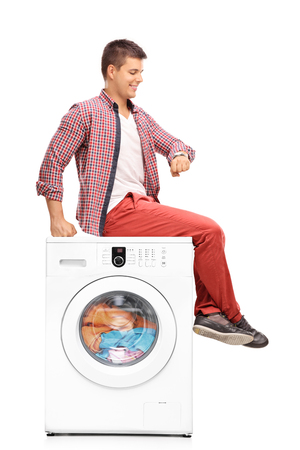 washing clothes: Vertical shot of a young man waiting for the laundry seated on a washing machine isolated on white background