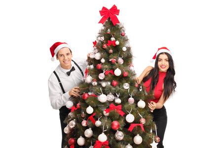 christmas hats: Young man and woman with Santa hats posing behind a Christmas tree isolated on white background Stock Photo