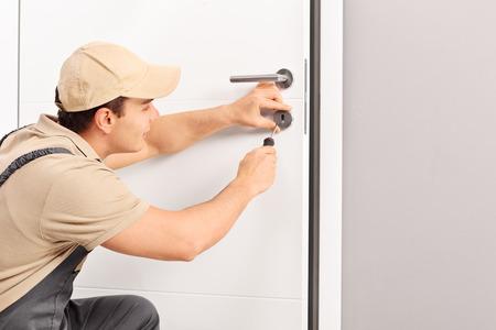 Junge männliche Schlosser eine Sperre auf eine neue Tür mit einem Schraubendreher die Installation