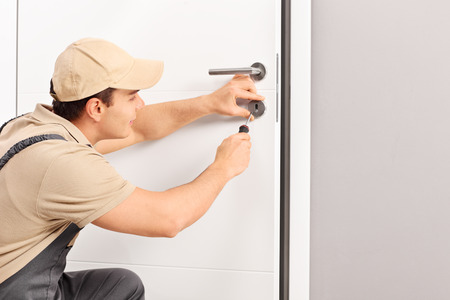 Young male locksmith installing a lock on a new door with a screwdriver Stock Photo