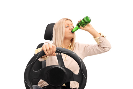 drinking driving: Studio shot of an irresponsible young woman drinking a beer and driving isolated on white background